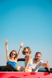 Lycklig familj som har gyckel i röd cabriolet arkivbild