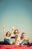 Lycklig familj som har gyckel i röd cabriolet fotografering för bildbyråer