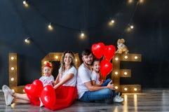 Lycklig familj som har gyckel på helgonvalentin dag i studio Föräldrar med små ungar med hjärtabaloons fotografering för bildbyråer