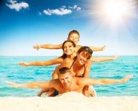 Lycklig familj som har gyckel på stranden royaltyfri fotografi