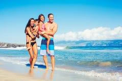 Lycklig familj som har gyckel på stranden fotografering för bildbyråer