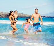 Lycklig familj som har gyckel på stranden royaltyfri foto