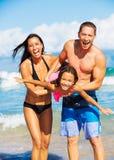 Lycklig familj som har gyckel på stranden royaltyfria bilder