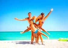 Lycklig familj som har gyckel på stranden Arkivbilder