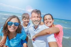 Lycklig familj som har gyckel på stranden tillsammans Rolig lycklig livsstil i sommarfritiden royaltyfria foton