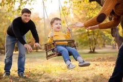 Lycklig familj som har gyckel på en gungaritt på en trädgård om höstdagen Royaltyfri Fotografi