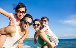 Lycklig familj som har gyckel på stranden Arkivfoto
