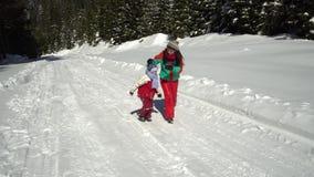 Lycklig familj som har gyckel som spelar i en snöig skog i bergen i vinter Mamman och hennes två barn sledding stock video
