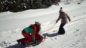 Lycklig familj som har gyckel som spelar i en snöig skog i bergen i vinter Mamman och hennes två barn sledding arkivfilmer