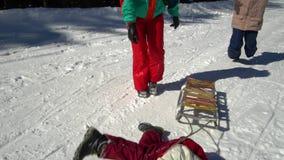 Lycklig familj som har gyckel som spelar i en snöig skog i bergen i vinter Mamman och hennes två barn sledding lager videofilmer