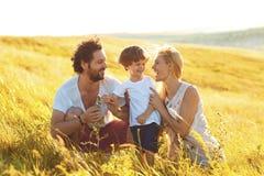 Lycklig familj som har gyckel som spelar i fältet arkivbilder