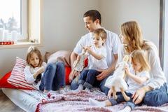 Lycklig familj som har gyckel tillsammans hemma i sovrum arkivbild
