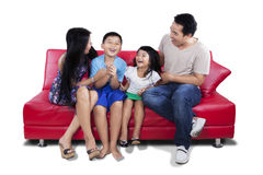 Lycklig familj som har gyckel tillsammans på soffan royaltyfria foton