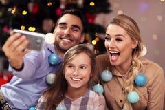 Lycklig familj som har gyckel under jultid och tar selfie arkivfoto
