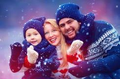 Lycklig familj som har gyckel under snö under vinterferier Arkivfoto