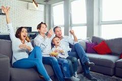 Lycklig familj som har hållande ögonen på TVsammanträde för gyckel arkivfoton