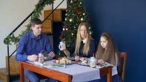 Lycklig familj som har julmatställen hemma arkivfilmer