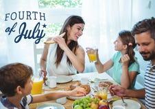 Lycklig familj som har lunch för 4th Juli Arkivbild