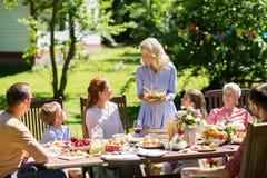Lycklig familj som har matställen eller det trädgårds- partiet för sommar fotografering för bildbyråer