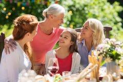 Lycklig familj som har matställen eller det trädgårds- partiet för sommar arkivfoto