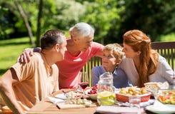 Lycklig familj som har matställen eller det trädgårds- partiet för sommar arkivfoton