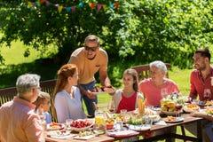Lycklig familj som har matställen eller det trädgårds- partiet för sommar royaltyfri foto