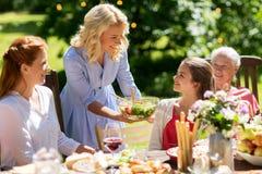 Lycklig familj som har matställen eller det trädgårds- partiet för sommar arkivbilder