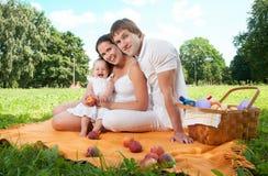 Lycklig familj som har picknick i parkera arkivfoton