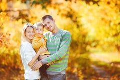 Lycklig familj som har rolig det fria i höst i parkera Arkivfoto
