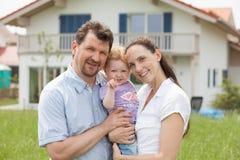 Lycklig familj som har roligt framme av huset Royaltyfri Fotografi