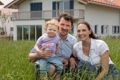 Lycklig familj som har roligt framme av huset Fotografering för Bildbyråer