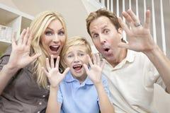 Lycklig familj som har sittande skratta för gyckel hemma Arkivbild