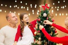 Lycklig familj som hemma dekorerar julträdet Fotografering för Bildbyråer