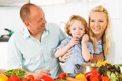 Lycklig familj som hemma förbereder en sund matställe. royaltyfri foto
