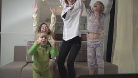Lycklig familj som hemma rotar för fotbollslaget Familjen hoppar upp och att jubla på det gjorde poäng målet Lycklig familjferie arkivfilmer