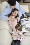 Lycklig familj som hemma ser foto Arkivfoton