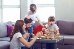 Lycklig familj som hemma spelar brädelekar royaltyfri foto
