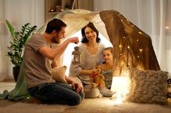 Lycklig familj som hemma spelar i ungetält på natten royaltyfri bild