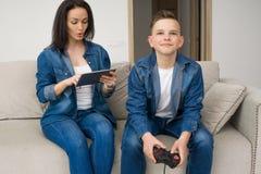 Lycklig familj som hemma spelar konsolen Fotografering för Bildbyråer