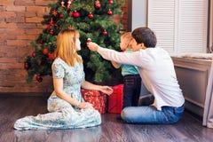 Lycklig familj som hemma spelar med julbollar royaltyfri fotografi
