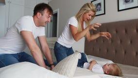 Lycklig familj som hemma spelar till kuddekampen på säng lager videofilmer