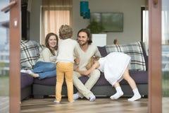 Lycklig familj som hemma spelar, ungar som har gyckel med föräldrar royaltyfri fotografi