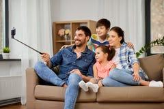 Lycklig familj som hemma tar selfie arkivfoto