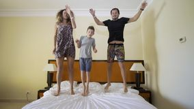 Lycklig familj som hoppar p? s?ngen lycklig begreppsfamilj Fadern, modern och pysen hoppar p? s?ngen lager videofilmer
