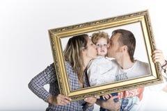 Lycklig familj som inramas av en bildram Arkivfoto