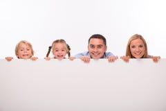 Lycklig familj som isoleras på vit bakgrund Arkivbild