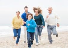 Lycklig familj som joggar på stranden arkivbilder