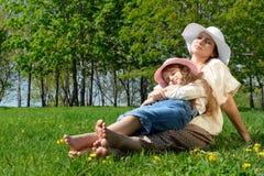 Lycklig familj som kopplar av i parkera Arkivfoto