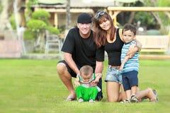 Lycklig familj som kopplar av i trädgården arkivbilder