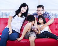 Lycklig familj som kopplar av på den röda soffan på lägenheten Arkivbild